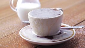 Cup full of spilled coffee and sugar on table. Unhealthy eating, diabetes, object and drinks concept - cup full of spilled coffee and sugar on wooden table with stock video footage