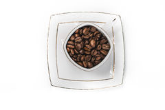 Cup fyllde med kaffebönor Arkivfoton