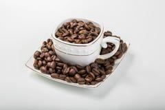 Cup fyllde med kaffebönor Arkivbild