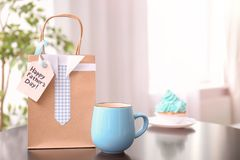 Cup and gift bag on table. stock images
