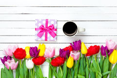 Cup and gift box near flowers Royalty Free Stock Photos