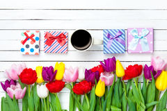 Cup and gift boxes near flowers Royalty Free Stock Photography
