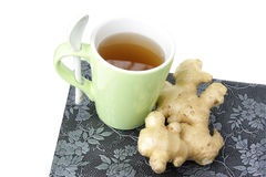 A Cup of ginger tea. On mat with fresh root Royalty Free Stock Photos