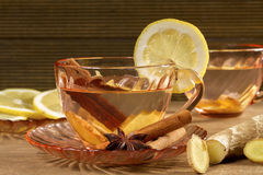 A cup of ginger tea with lemon, cinnamon and anise stars. Royalty Free Stock Photo