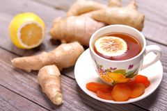 A cup of ginger tea with lemon, ginger roots and dried apricots royalty free stock photo