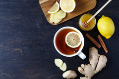 Cup of ginger tea with lemon and honey on dark background. Top view. Antiviral Healthy useful drink. Stock Photos