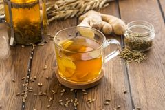 Cup of ginger tea with lemon and wheat spike on wooden table. Side view royalty free stock photos