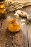 Cup of ginger tea with lemon and wheat spike on wooden table. Side view stock image