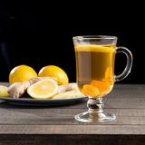 A cup of ginger tea with lemon on a wooden background. A transparent glass filled with ginger tea with lemon. On a blue wooden table. Yellow lemon Royalty Free Stock Image