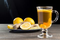 A cup of ginger tea with lemon on a wooden background. A transparent glass filled with ginger tea with lemon. On a blue wooden table. Yellow lemon Royalty Free Stock Photography