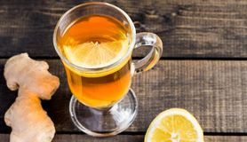 A cup of ginger tea with lemon on a wooden background. A transparent glass filled with ginger tea with lemon. On a blue wooden table. Yellow lemon Stock Image
