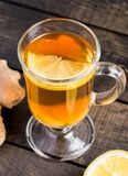 A cup of ginger tea with lemon on a wooden background. A transparent glass filled with ginger tea with lemon. On a blue wooden table. Yellow lemon Stock Photo