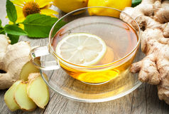 Cup of ginger tea. With lemon on wooden table stock photography