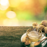 Cup of ginger tea with smoke and cookie on grunge wooden table i Royalty Free Stock Photography