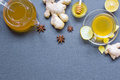 Cup of ginger tea and teapot with lemon, honey and spices. Transparent cup of ginger tea and teapot with lemon, honey and spices on gray stone background with Royalty Free Stock Photography