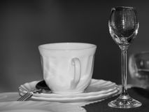 Cup and glass on the table in restaurant, black and white photo. Stock Photo