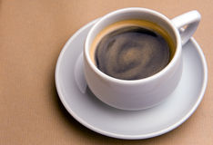Cup of gold. A porcelain coffee cup on a saucer on a light brown background Stock Photos