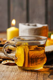 Cup of golden tea in evening candle light Stock Image