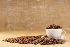 Cup with grains of coffee and a smoke. Royalty Free Stock Photo