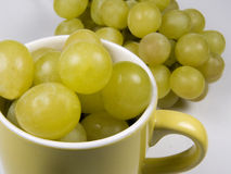 Cup of grapes. A coffee cup full of white grapes Stock Images