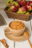 Cup of grated apples with cinnamon. Cup of freshly grated apples with cinnamon, placed on a white vintage wooden board, with a wooden spoon and three sticks of Stock Image