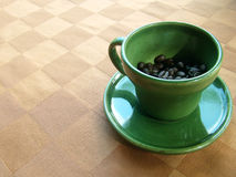 Cup green coffee ceramic. Green coffee cup with coffee beans inside Placed on the leather tablecloth stock photography