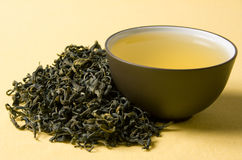 Cup of green tea. Clay cup with green tea in dried tea leaves Stock Photography