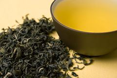 Cup of green tea. Clay cup with green tea in dried tea leaves Royalty Free Stock Photography