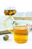 Cup of green tea against the opened books. Cup of green tea with a lotus against the opened books Stock Photo