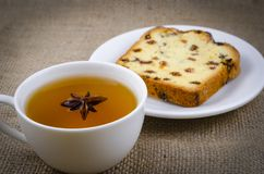 A cup of green tea with an anise-star and a delicious piece of cake royalty free stock photo