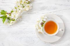 Cup of green tea and branches of blossoming cherry on old wooden background. Cup of green tea and  branches of blossoming  cherry   on old  wooden  background Royalty Free Stock Photo