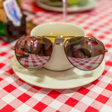 Cup of green tea on a checkered tablecloth with sunglasses. A cup of green tea on a checkered tablecloth red and white. Sunglasses with the reflection of a cafe royalty free stock images
