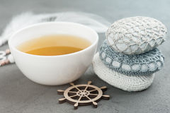 Cup of green tea and crocheted pebbles Stock Photo