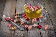 Cup of green tea with dried roses Royalty Free Stock Photos