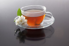 Cup with green tea and  fresh  jasmine flowers Stock Photos