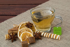 A cup of green tea. Glass cup green tea on burlap tablecloth old wooden table with two lumps of brown sugar and decorated with cinnamon and dried orange anis Stock Photo