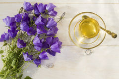 Cup of green tea in a glass Cup and a bouquet of bells royalty free stock photography