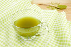 The cup of green tea on green cotton fabric Royalty Free Stock Photos