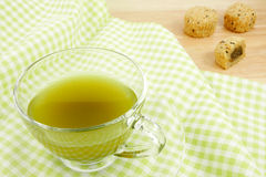 The cup of green tea on green cotton fabric Stock Image