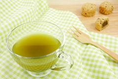 The cup of green tea on green cotton fabric Royalty Free Stock Photography