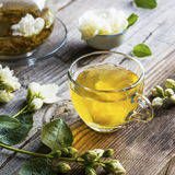 Cup of green tea infused with jasmine on a gray wooden background Royalty Free Stock Photos
