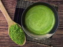 A cup of green tea latte on bamboo mat and matcha powder in spoon on wooden background stock image
