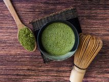 A cup of green tea latte and matcha powder in spoon with bamboo whisk on wooden background royalty free stock photo
