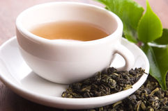 Cup of green tea with leaves Royalty Free Stock Photo
