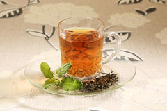 Cup with green tea and leaves Stock Photos