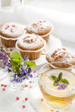 Cup of green tea with lemon balm and tasty muffins with sugar hearts Royalty Free Stock Photography