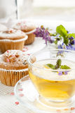 Cup of green tea with lemon balm and tasty muffins with sugar hearts. Blue spring flowers viola on light background Royalty Free Stock Photos