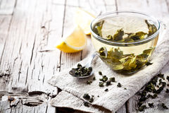 Cup of green tea and lemon. On rustic wooden table Royalty Free Stock Photo