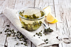 Cup of green tea and lemon. On rustic wooden table Royalty Free Stock Photos