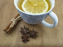 A cup of green tea and a lemon wedge on a wooden table with cinnamon sticks and aniseed flowers. Porcelain cup with tea and lemon on a wooden table of brown royalty free stock images